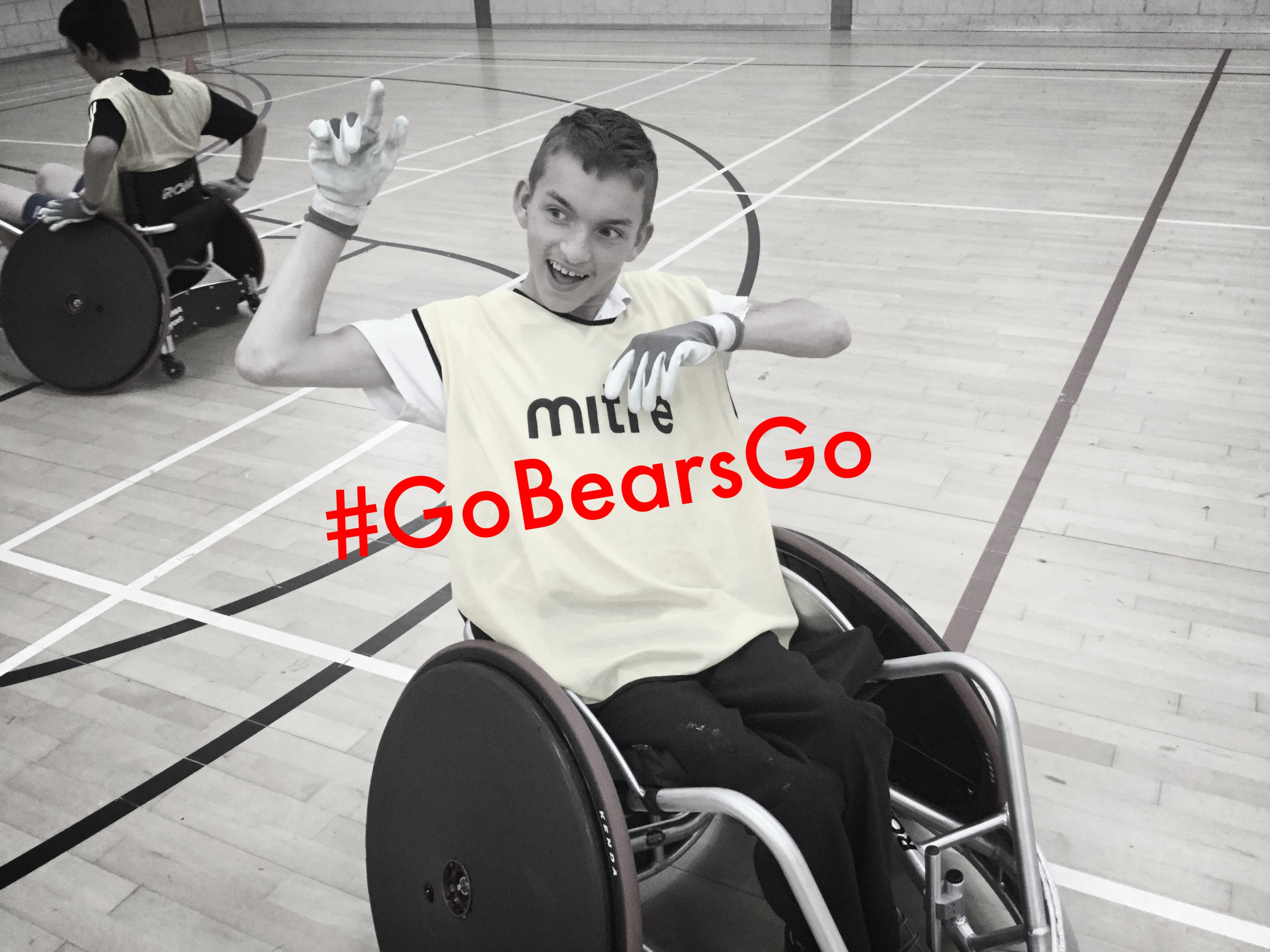 Young player with cerebral palsy having fun playing wheelchair rugby with friends.