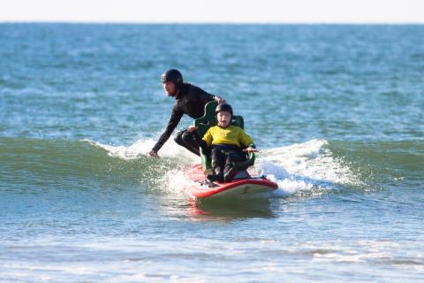 Riding a wave on our seated tandem surfboard for wheelchair users
