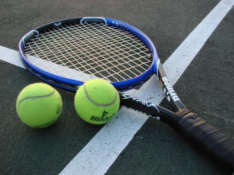 tennis racket and 2 tennis balls lying on a tennis court