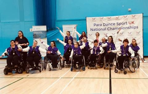 Freewheelin dance group pose in front of a banner saying 'Para Dance Sport UK National Championships'. They wear purple tops and their gold medals round their necks.