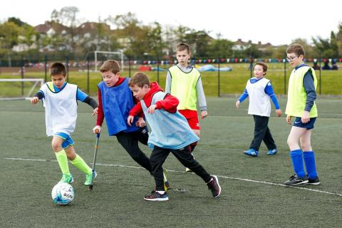 Action shot of youth pan disability football session - young boys kicking the football