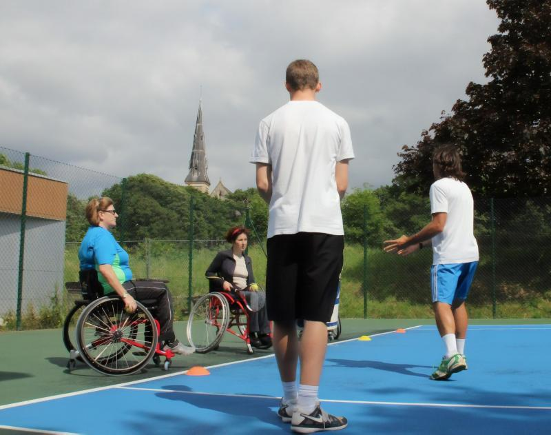 Wheelchair users playing tennis with coaches