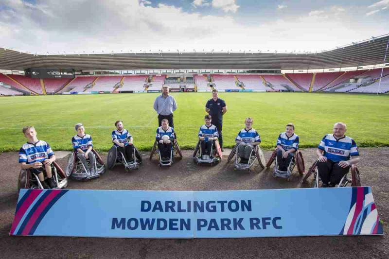 Wheelchair Users gather round a sign reading Darlington Mowden Park RUFC