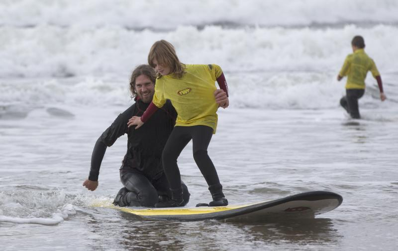 A visually impaired surfer, surfing tandem with a Surfability coach