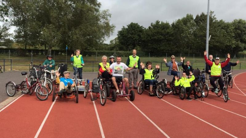 A group of people on a flat athletics track all sat upon different types of bicycles