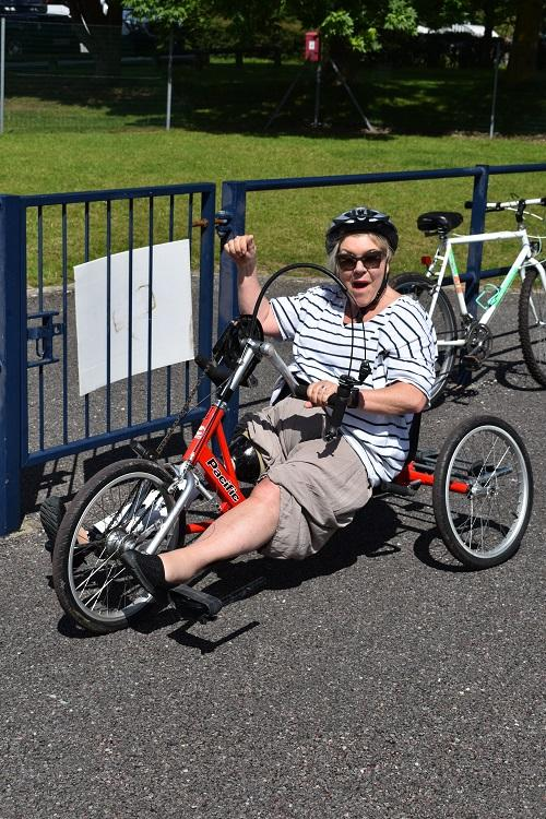 A woman sat upon a hand cycle, smiling in the sun.