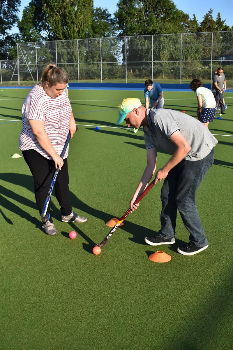 Male and female young adults dribbling a hockey ball.