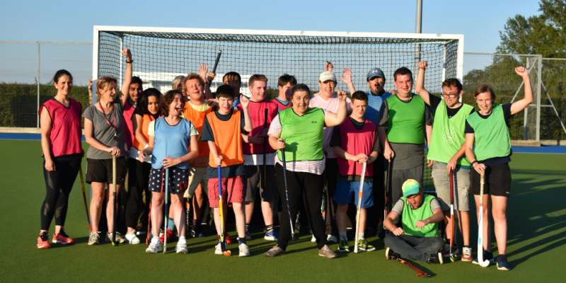 Group photo of young adults wearing sports clothing and bibs , smiling in front of a hockey goal. Some are holding hockey sticks.