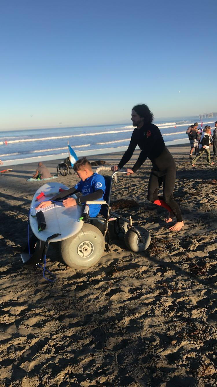 Coach Ben with prone surfer Ethan showing his beach wheelchair and prone surfboard
