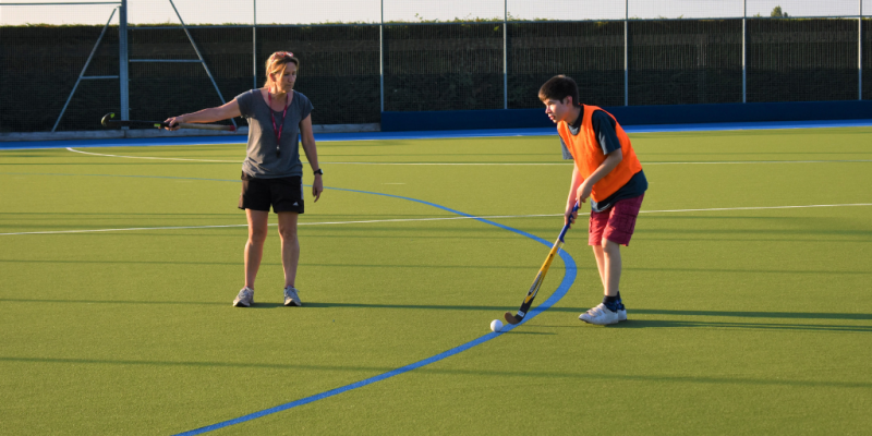 A female coach points towards the direction that they want the young male participant to dribble towards with their hockey stick.