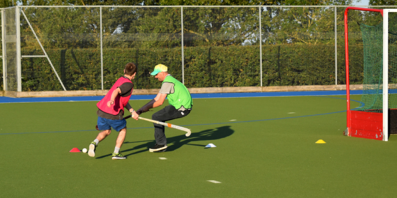 Two male participants are playing a competitive hockey game. Both are wearing bright colours.