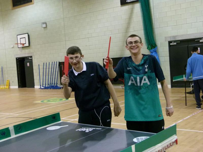 Two young table tennis players waving to camera