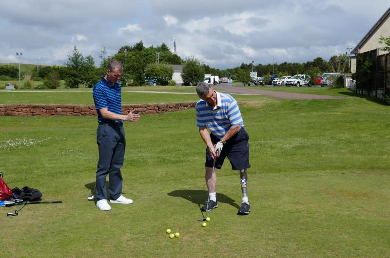 SDGC participant about to hit a ball from the fairway with Golf Pro watching and giving tips