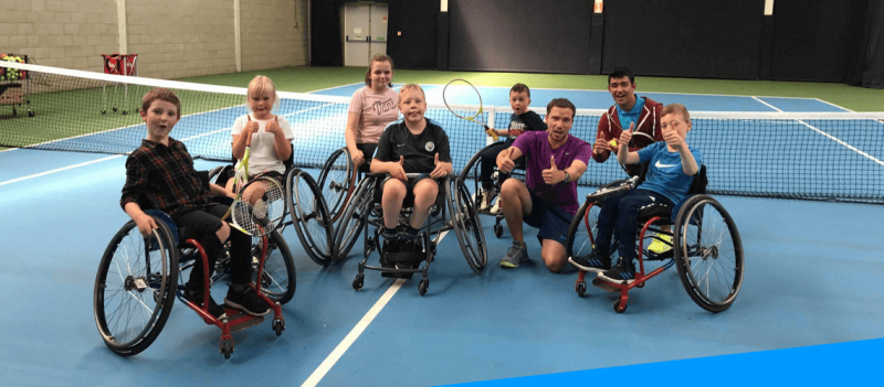 group of young children in wheelchairs with tennis rackets on the tennis court