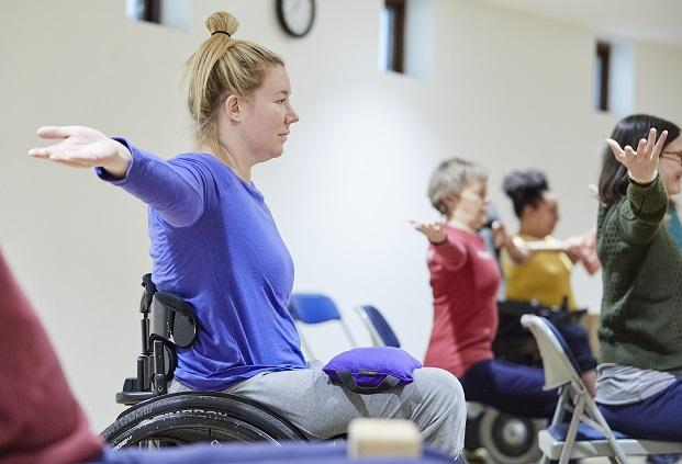 Wheelchair user with blond hair tied up in a top knot wearing a blue shirt extending her arms out to the side with a sandbag on her lap to help ground her in the yoga pose , other students, one in a red top, one in a yellow top an one in a green top all mimic the pose in the background