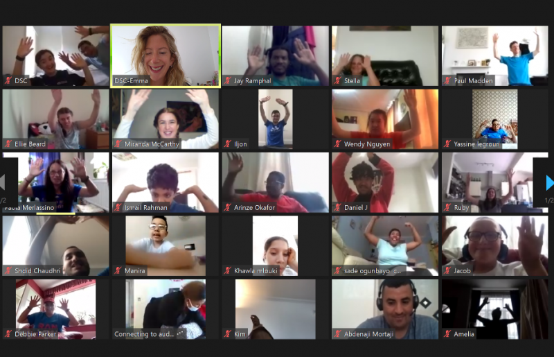 A screenshot of a Zoom meeting showing 25 participants all with their arms raised and smiling during an Adaptive Yoga Live online session. The participants are various ages, races, and a mix of male and female.