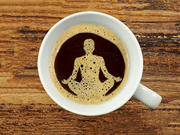 A wooden table with a white coffee cup filled almost to the top with black coffee, the bubbles are shaped like a yogi, sitting cross-legged, hand resting on the knees, with index fingers and thumbs touching