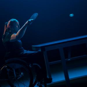 female wheelchair user plays a shot at table tennis