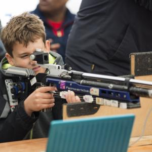 a boy tries shooting on a rifle range