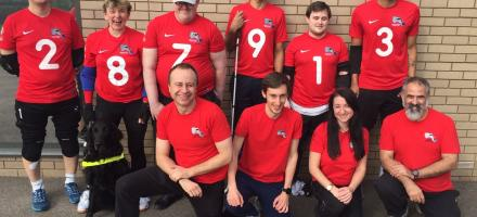 Group picture of players and volunteers in red club kit