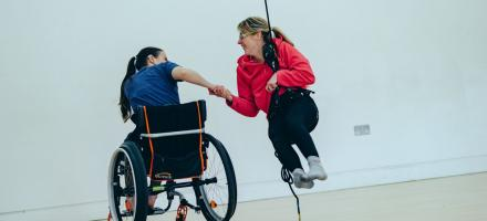 2 women dance together. 1 is using her wheelchair to move the other who is suspended in an aerial harness