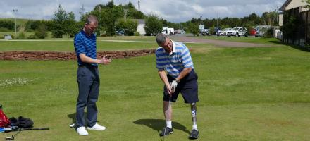 an SDGC member getting tips and lesson from a golf-pro