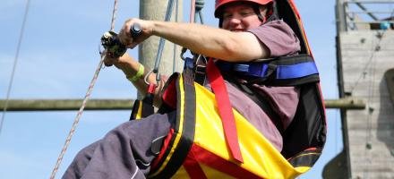 young boy in high ropes harness