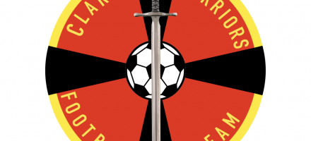 The club badge resembles a red shield bordered in yellow with a football at the centre of a black cross on the shield and a sword overlain in a vertical position.